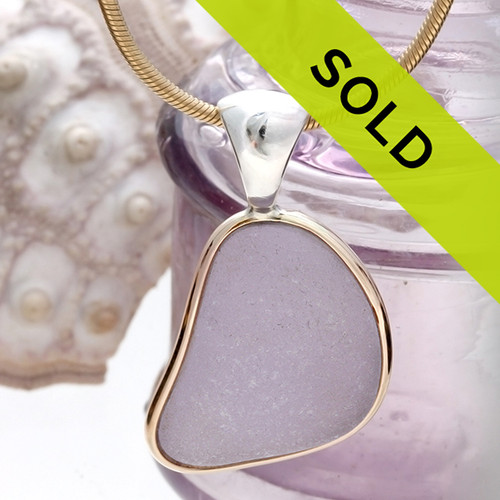 This sea glass is fused through with Vivid Purple or Lavender from Maine. It is set in a mixed metal gold and sterling silver Deluxe Wire Bezel setting. Very Versatile and elegant. CLASSIC!  This setting leaves this amazing natural sea glass piece just the way it was found on  the beach!
