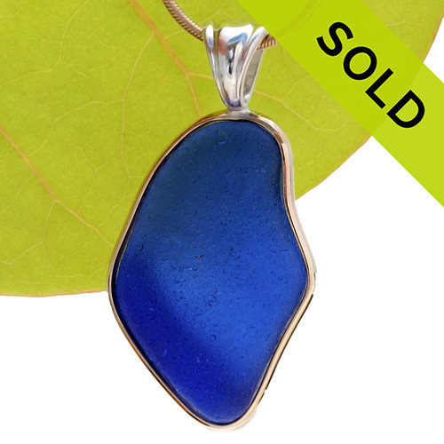 A HUGE piece of rich cobalt blue sea glass set in our classic and elegant Tiffany Deluxe Wire Bezel setting in a mixture of gold and silver. This setting leaves the sea glass piece totally UNALTERED from the way it was found on the beach. Sorry this one of a kind sea glass pendant has been sold!