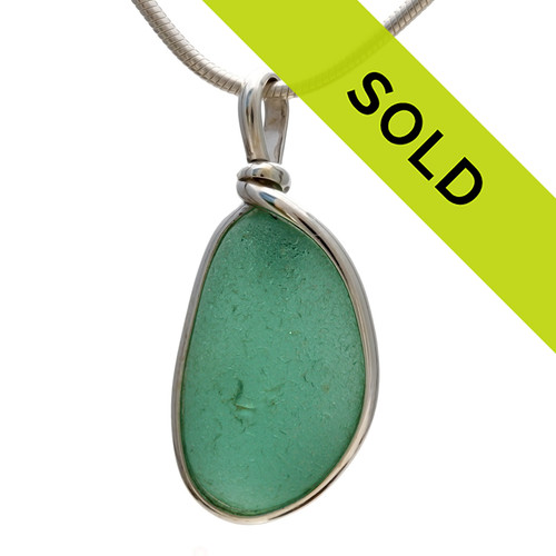 A glowing perfect piece of beach found glass from Seaham England in a stunning deep aqua green is set in our Original Wire Bezel© pendant setting. Sorry this sea glass jewelry piece has already been sold!