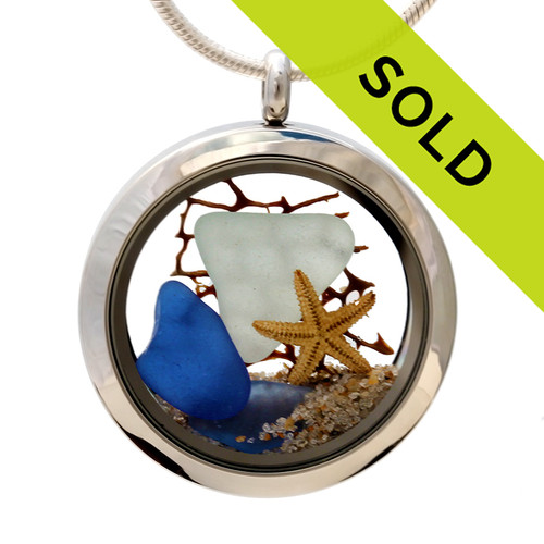 Genuine pale aqua and blue sea glass combined with a vintage sea fan and real shells completed with real beach sand. So sorry this locket has been sold!