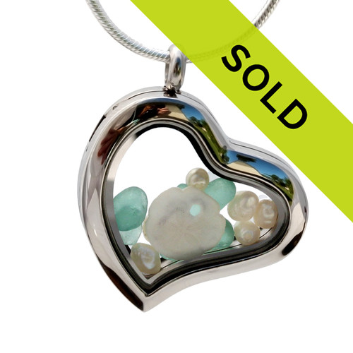 Small bits of tropical aqua sea glass pieces combined with real pearls and a sandollar in a feminine heart shaped locket magnetic stainless steel locket necklace!