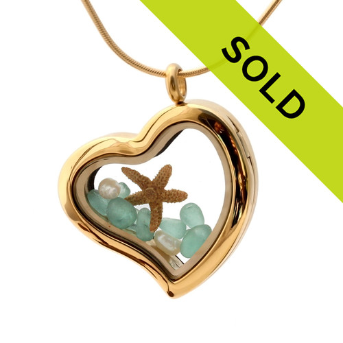 Small aqua sea glass pieces combined with a starfish and pearls  in a feminine heart shaped locket.