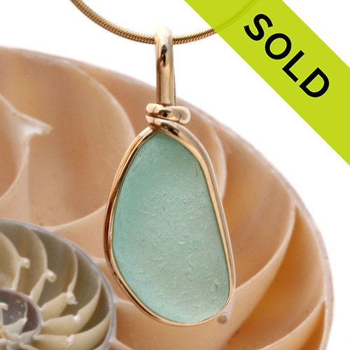 A perfect longer piece of medium aqua blue with in our signature Original Wire Bezel© pendant setting that leaves both front and back open and the glass unaltered from the way it was found on the beach. Sorry, this Sea Glass Pendant has been SOLD!