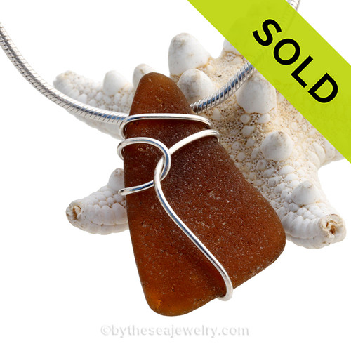 A nice piece of genuine sea glass in amber brown and a simple deco inspired wire wrapped sterling setting. Sorry this piece of sea glass jewelry has been sold!