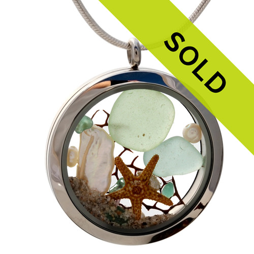 Genuine seafoam green and aqua sea glass pieces combined with a real starfish, pearls and real beach sand in this 35MM stainless steel waterproof locket. Sorry this sea glass jewelry piece has been SOLD!