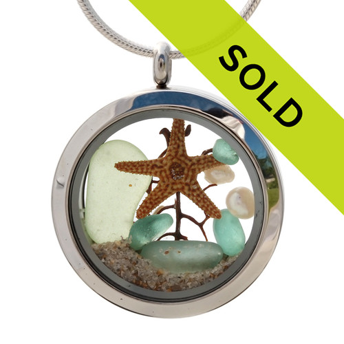 Genuine seafoam green and aqua sea glass pieces combined with a real starfish, pearls and real beach sand in this 30MM stainless steel locket.