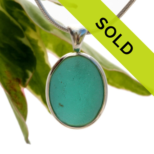 A neat  interesting piece of vivid aqua sea glass from the UK in our In NEW Deluxe Sterling Wire Bezel© Setting that leaves the glass just the way it was found on the beach.  Sorry this sea glass jewelry piece has been sold!