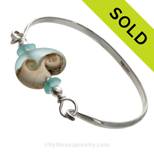 Two pieces of beach found sea glass in aqua on this solid sterling silver half round sea glass bangle bracelet. The center bead is handmade by a glass artist and resembles the ocean and beach. SOLD - Sorry this Sea Glass Bangle Bracelet is NO LONGER AVAILABLE!