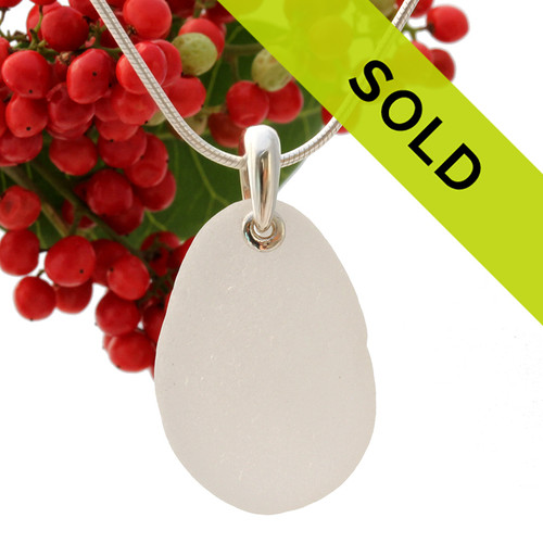A larger piece of perfect piece of pure white sea glass with a solid sterling bail finished with sterling detail.
