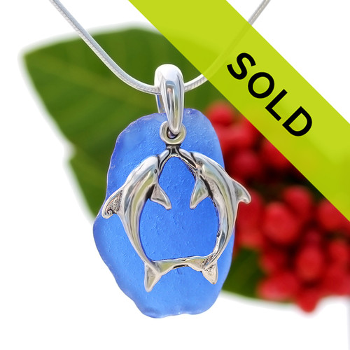 Beach found cobalt blue sea glass is combined with a solid sterling bail and finished with a S/S Sea Kissing Dolphin  Charm on an 18 Inch solid sterling snake chain.
