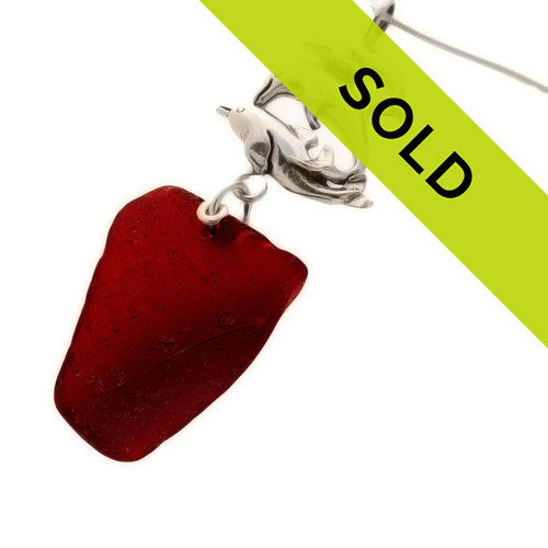 This red sea glass necklace is complimented with a solid sterling silver dolphin charm. Perfect for any sea glass lover!