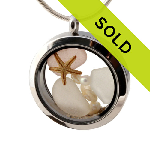 White, rare depression pink and yellow sea glass combined with a real starfish, pearls, sea fan, tiny shells and real beach sand in this 30MM stainless steel locket.