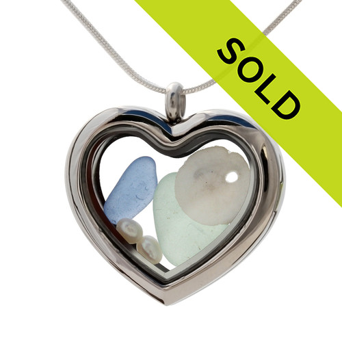 Our new heart lockets make this green and light blue sea glass really shine! A tiny sandollar and fresh water pearls completes the beachy look! Genuine beach found glass.
