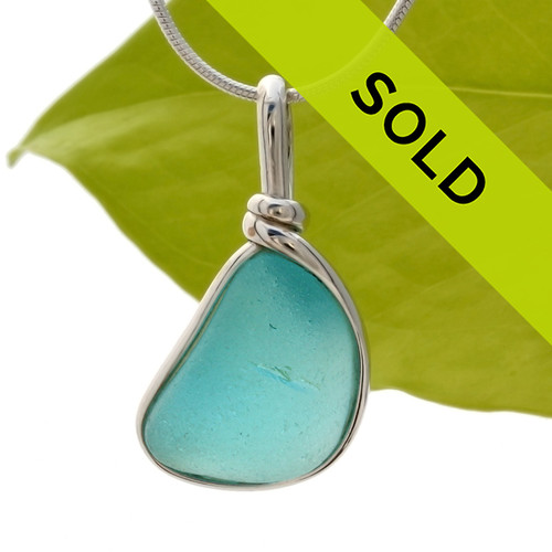 A vivid piece of electric vivid aqua blue sea glass set in our Original Wire Bezel© pendant setting in solid sterling silver. Sorry this sea glass jewelry selection has been sold!