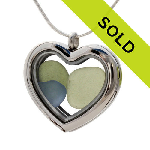 Green and Carolina Blue sea glass heart combined a large silver heart in this sea glass locket necklace.