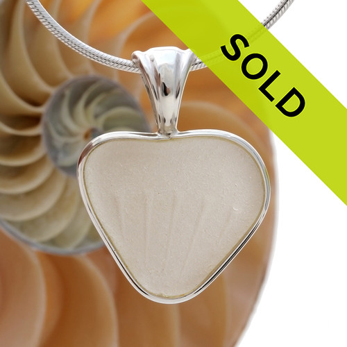 A beautiful white natural sea glass heart set in our deluxe wire bezel setting. Genuine sea glass hearts are a RARE phenomena and cherished among sea glass lovers! This one is unique as it has distinct embossing that radiates from the point.