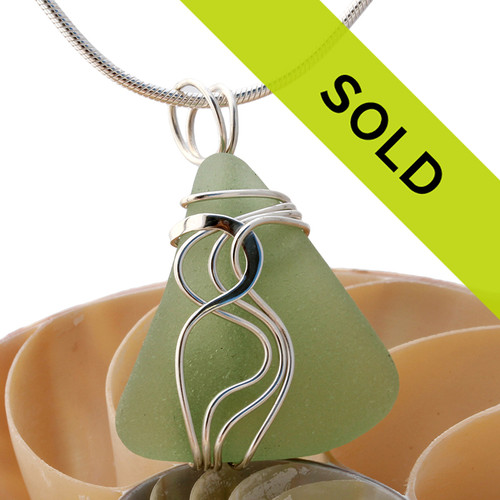 A nice TOP QUALITY piece of pale olive or seafoam green sea glass set in our signature Waves© setting in sterling silver. Sorry this sea glass jewelry piece is no longer available.