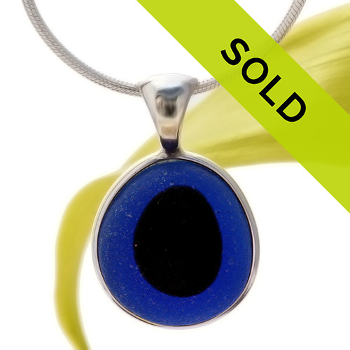This sea glass is fused vivid deep dark blue eye with a perfect black center.  It is set in our sterling silver Deluxe Wire Bezel© setting.