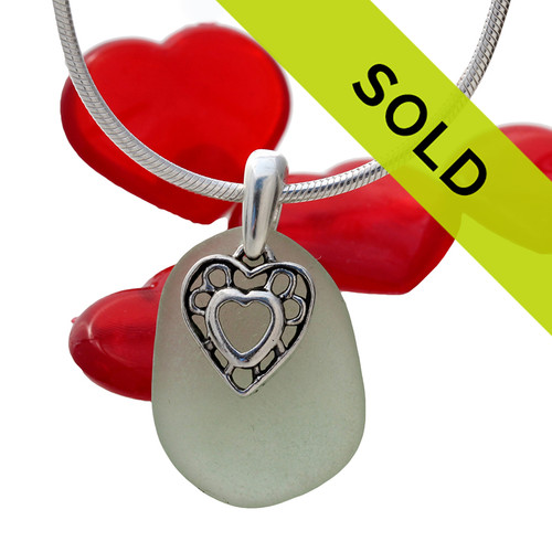 A perfect piece of natural pale olive green sea glass set on a solid sterling hand cast bail with a sterling silver heart in hearts charm. Sorry this sea glass necklace has been sold!