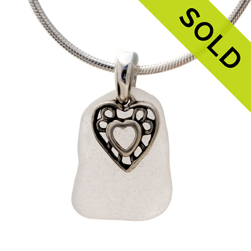 A nice piece of natural pure white sea glass set on a solid sterling hand cast bail with a sterling silver heart in hearts charm. Sorry this Sea Glass Necklace has been SOLD!