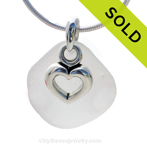 A perfect piece of natural pure white sea glass set on a solid sterling hand cast bail with a sterling silver heart in hearts charm.