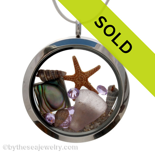 Sorry this sea glass jewelry piece has been sold! February Sea Glass & Birthstone Locket Necklace Purple or Amethyst RARE sea glass combined with a real starfish, tiny shells, a square abalone shell brightened up with purple or amethyst gems in a 35MM  Jumbo Twist Top Waterproof Locket.