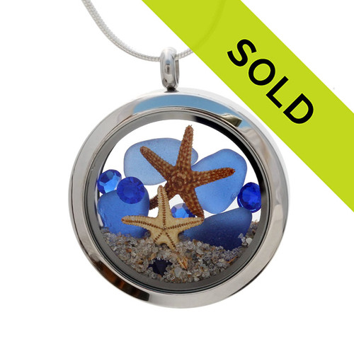 A beautiful pieces of natural blue sea glass combined in a stainless steel locket necklace with two real starfish and finished with Sapphire Blue gemstones. Sorry this sea glass jewelry item has been sold!
