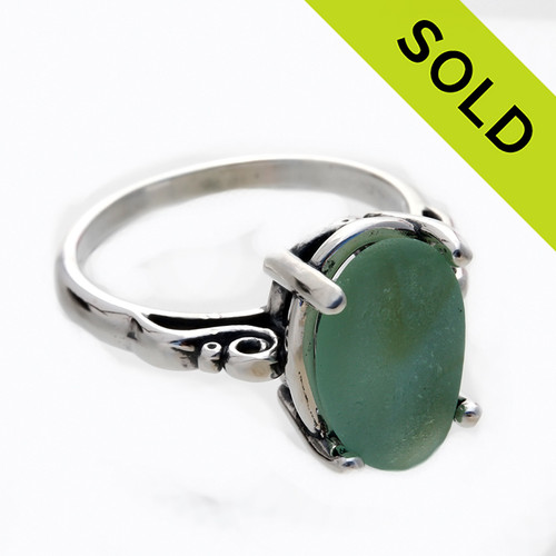 A natural UNALTERED pure mixed green sea glass piece set in a sterling silver scroll ring.