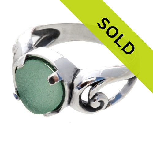An unaltered beach found aqua green sea glass ring set in a simple sterling swirl setting.