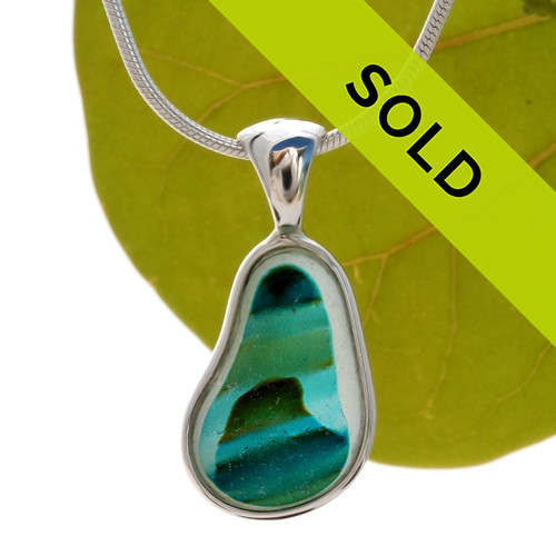 A beautiful pure white base holds deep teal, green and vivid aqua in sea scene in this Seaham Sea Glass Multi set in our timeless, classic Deluxe Wire Bezel© setting in solid sterling silver. Sorry this sea glass jewelry selection has been sold!