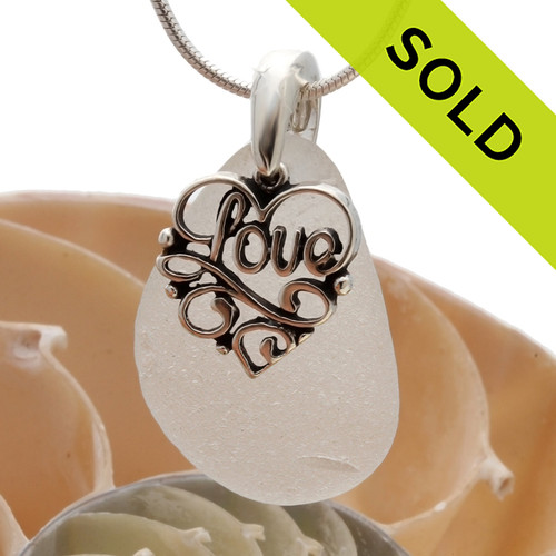 "A perfect piece of pure white genuine sea glass with a solid sterling bail and detailed ""Love"" heart charm. SOLD - Sorry This Sea Glass Necklace Is NO LONGER AVAILABLE!"