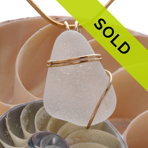 Sorry this sea glass jewelry item has been sold! A neat Top Quality triangular shaped piece of beach found White Genuine Sea Glass in a simple wire wrapped Gold Pendant Setting.