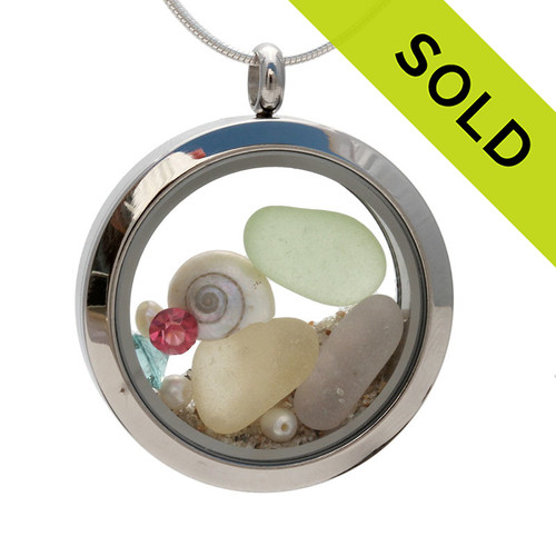 Genuine pale green, lavender, yellow sea glass combined with a real tiny nautilus shells,  pearls, real beach sand , and crystal gems  in this medium 30MM stainless steel locket. Sorry this piece has been SOLD!