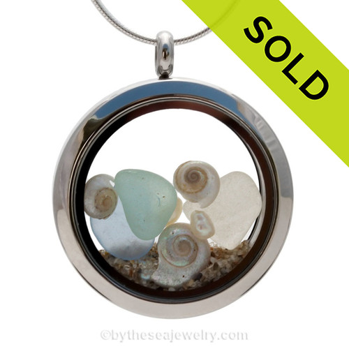Soft aqua green, light blue and white sea glass combined with pearlized mini nautilus shells and fresh water pearls. Beach sand makes this your own personal beach on the go! Sorry this sea glass locket has been sold!