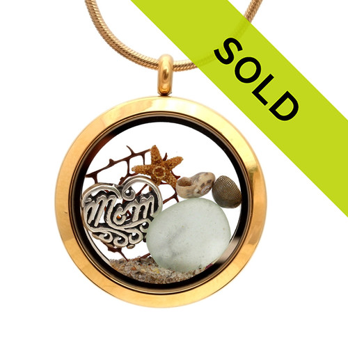 """A stunning goldtone stainless steel locket necklace with a seafoam green sea glass pieces and a """"MOM"""" Charm. The locket contains shells, a bit of seafan, a baby starfish and real beach sand. Sorry this sea glass jewelry piece has been sold!"""