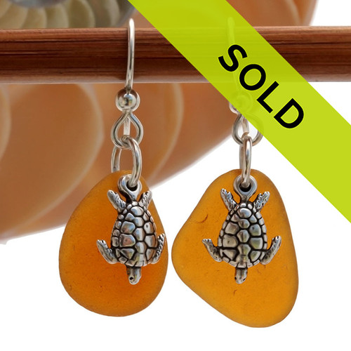 Genuine Sea Glass Earrings in Amber Brown With Solid Sterling Starfish Charms These are 2 perfect TOP QUALITY pieces of perfect amber Certified Genuine Sea Glass in a simple sterling setting with Solid Sterling Silver sea turtle charms.  Sorry this sea glass jewelry selection has been sold!