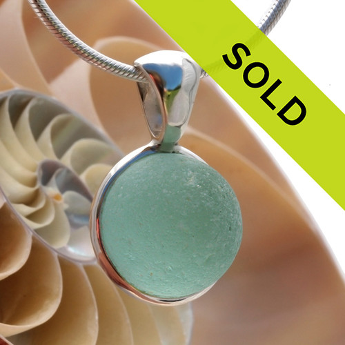 A stunning electric aqua sea glass marble mixed with white opaque glass in our Deluxe Wire Bezel© pendant setting. Sorry this sea glass jewelry piece has been sold!