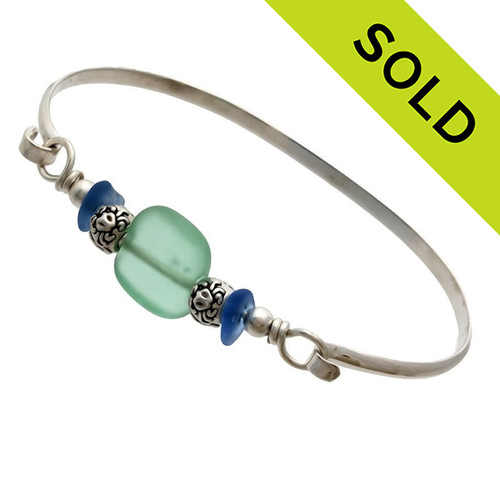 Two pieces of beach found sea glass in bright blue on this solid sterling silver sea glass bangle bracelet. The center bead is handmade by a glass artist and resembles bright green sea glass. Finished with sea life beads that have images of a crab, starfish and a sea gull. SOLD - Sorry this Sea Glass Bangle Bracelet is NO LONGER AVAILABLE!
