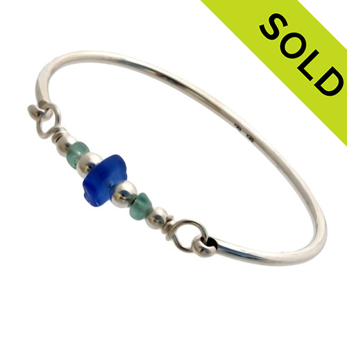 Three pieces of beach found sea glass in tropical aqua and a rich cobalt blue on this solid sterling silver full round sea glass bangle bracelet.