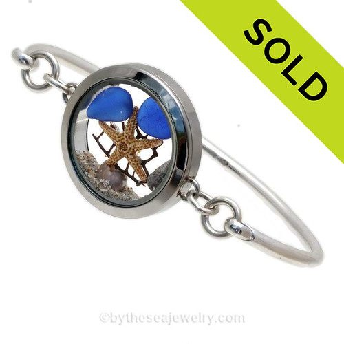Genuine Sea Glass Locket Bracelet Tiny cobalt blue genuine sea glass combined with a small starfish,shells, a bit of vintage seafan and finished with real beach sand in this one of a kind sea glass bangle bracelet!  Sorry this Sea Glass Jewelry selection is no longer available.