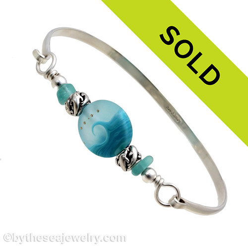 Two pieces of beach found sea glass in vivid tropical aqua on this solid sterling silver half round sea glass bangle bracelet.  Sorry this sea glass jewelry piece has been sold!
