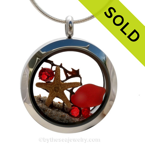 Beautiful and rare piece of ruby red sea glass combined in a stainless steel locket with a real starfish, a bit of seafan and sand from the beaches of Florida. Sorry this sea glass jewelry selection has been sold!