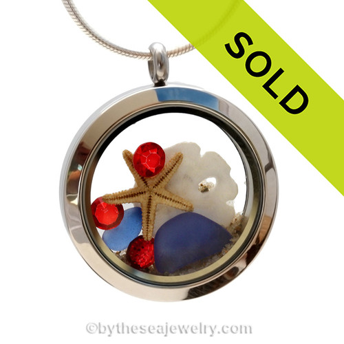Genuine Blue  Sea Glass combined in a stainless steel locket with a real starfish, a small sandollar and sand from the beaches of Florida. Ruby Red gemstones bring it all together for a patriotic summer sea glass locket. Sorry this sea glass jewelry piece is no longer available.
