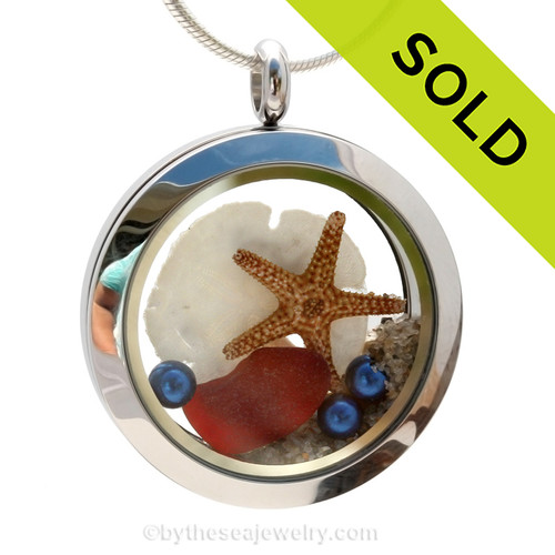 Beautiful and rare piece of ruby red sea glass combined in a stainless steel locket with a real starfish, a baby sandollar and sand from the beaches of Florida. Blue pearls finish the patriotic piece. Sorry this sea glass jewelry piece has been sold!