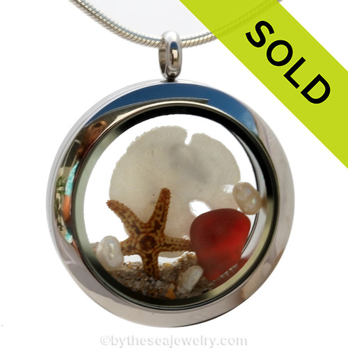 Beautiful and rare piece of ruby red sea glass combined in a stainless steel locket with a real starfish, a baby sandollar and sand from the beaches of Florida. Pearls finish the piece in elegance. Sorry this sea glass locket has been sold!