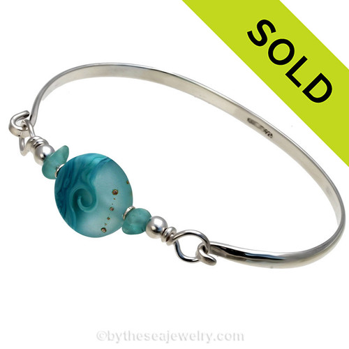 Two pieces of beach found sea glass in vivid tropical aqua on this solid sterling silver half round sea glass bangle bracelet.  Sorry this piece of sea glass jewelry has been sold!