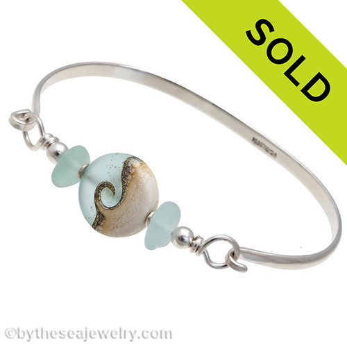 Two pieces of beach found Genuine Sea Glass in pale aqua on this solid sterling silver half round sea glass bangle bracelet.