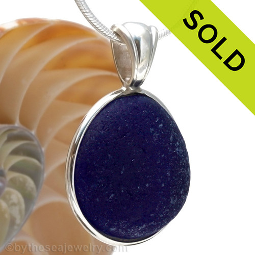 A stunning thick piece of genuine UNALTERED sea glass in an elegant setting.A perfect and LARGE piece of vivid Midnight Blue sea glass from the UK in our In Deluxe Sterling Wire Bezel© Setting that leaves the glass just the way it was found on the beach.  Sorry this one of a kind sea glass jewelry piece has been sold!