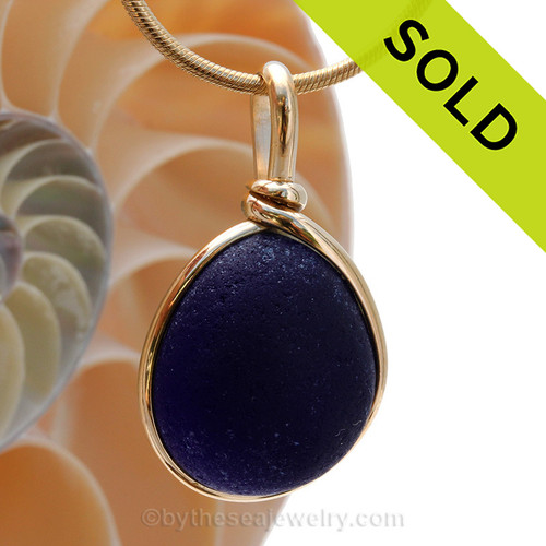 A perfect piece of vivid Deep Midnight Blue sea glass from the UK set in our Original Wire Bezel© Setting in 14K Rolled Gold. A setting that leaves the glass just the way it was found on the beach. SORRY this piece of sea glass jewelry has been sold!