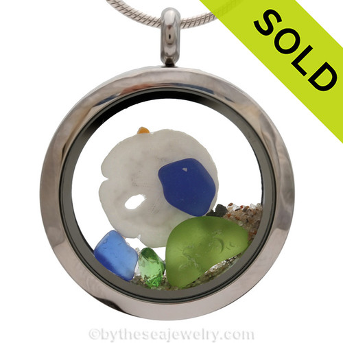 Genuine lime green and cobalt blue sea glass piece combined with a real mini sandollar and a real beach sand in this stainless steel locket. Finished with vivid peridot crystal gems for a bit of beachy bling. Sorry this sea glass jewelry selection has been sold!